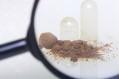 Look through the magnifying glass. The brown pills are scattered over the white surface. One active ingredient is poured from one pill Stock Image