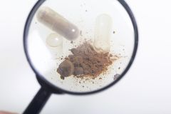 Look through the magnifying glass. The brown pills are scattered over the white surface. One active ingredient is poured from one. Pill Royalty Free Stock Photo