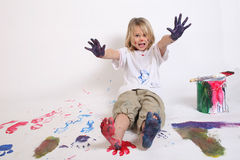 Look at me!. A young girl painting a great big mess with bright colors stock image