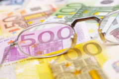 Look at the money. Glasses placed on euro banknotes for your financial, bonus, cashback, gifts and presents copy - note, that the money is real and used Royalty Free Stock Images