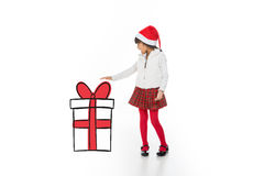 Look at my christmas present. Asian child showing her xmas gift with a surprise expression royalty free stock photography