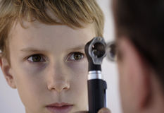 Look into my ey. Image of a young boy undergoing an examination by a doctor using an ophthalmascope Royalty Free Stock Photo