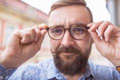 Look into my eyes. Bearded fashion man wearing stylish glasses Stock Photography