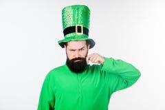 Look at my moustache. Bearded man celebrating saint patricks day. Hipster in leprechaun hat and costume twirling. Moustache. Happy saint patricks day. Irish man royalty free stock photo