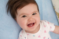 Look at my teeth. Excited baby girl smiling widely to show her first teeth Stock Photography