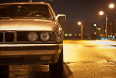 Look of old BMW. Golg old BMW of 5 series, front view. Street night from lamps. Night scene, car in the light of lamps Royalty Free Stock Photo