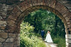 Look through the old stone arch on the stylish newlywed couple holding hands and walking along the path of the green. Forest Royalty Free Stock Images