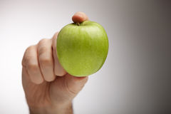 Look at this one. Male hand holding an apple with two fingers. Studio shot taken with 5d mark II and 70-200 2.8L IS Stock Images