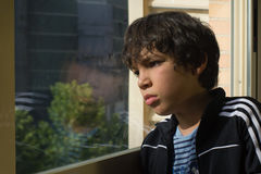 Look out. A sad boy looking out through a window Royalty Free Stock Image