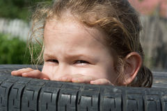 Look out. Naughty girl watch out of the tires Royalty Free Stock Image