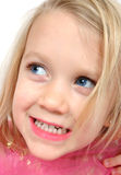 Look over here!. Little girl with big blue eyes looks up and gives a cheesy grin Royalty Free Stock Photo