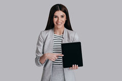 Look over here!. Beautiful young woman in smart casual wear pointing copy space on her digital tablet and smiling while standing against grey background royalty free stock photo