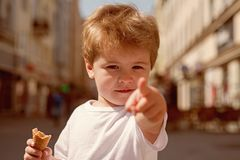 Look over there. Little child point finger on city street. Small boy with stylish haircut. Little child with short blond. Hair. Healthy hair care habits. Hair stock photos