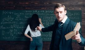 Look over there. Teacher man in glasses with textbook point at girl student rear view. Woman write equation on. Look over there. Teacher men in glasses with stock image