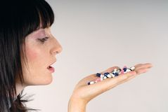 Look at pills!. Young woman look at colours pills Royalty Free Stock Image