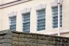 Windows of a prison building with bars. A look at the prison building from the oute. Metal lattice on windows royalty free stock image