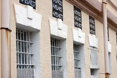 Windows of a prison building with bars. A look at the prison building from the oute. Metal lattice on windows stock images