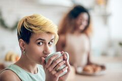 Face of young woman looking with interest with cup