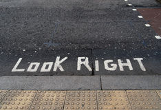 Look right written on tarmac road. Political metaphor maybe. Royalty Free Stock Photo
