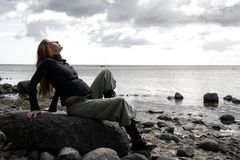 Look into the sky. A young pregnant woman sits at the beach on a stone and looks into the sky Stock Photo