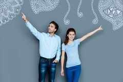 Emotional people pointing to different directions while travelling. Look there. Cheerful active young people pointing to different directions while choosing Stock Photography