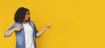 Free Look There. Smiling Afro Girl Indicating Copy Space On Yellow Background Stock Image - 179706241