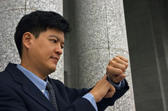 Look At The Time!. Asian man in a business suit looking at his watch royalty free stock photo