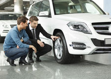 Look at these tires! Young car salesman showing the advantages o royalty free stock photography