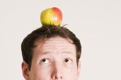 Look to the apple on head. Close up of face of young man with apple on the head Stock Photo