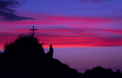 Look To The Cross. A man kneeling and looking up to a cross on a hill at sunset Stock Image