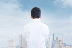 Look to The Future. Asian Businessman Looking Forward To Big City Background Royalty Free Stock Image