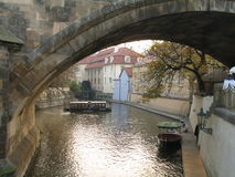 Look under the arches of the Gothic Charles Bridge on the water with boat Royalty Free Stock Photos