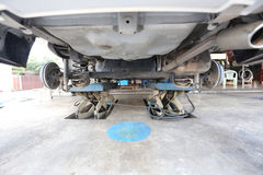 Look under the car at inspection for maintenance. Look under the car at inspection for maintenance in garage shop Royalty Free Stock Photo