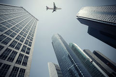 Look up at aircraft is flying modern urban office buildings in S Royalty Free Stock Photo