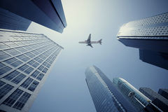 Look up at aircraft is flying modern urban office buildings in S. Looking up at aircraft flying over the modern urban office buildings backgrounds at Shanghai Royalty Free Stock Photo