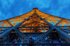 Look up from one of the platforms of the illuminated Eiffel Tower in Paris, France. Paris, France - October 16, 2016: look up from one of the platforms of the Royalty Free Stock Photos