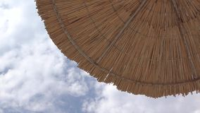 Look up straw umbrella and clouds motion. UHD 4K stock video footage