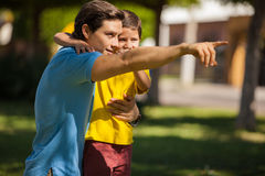 Look up there son. Young Latin father pointing and showing something to his cute son outdoors Stock Photography