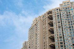 A look up to a newly constructed Chinese apartment with a nice blue sky. royalty free stock photography