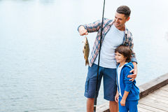Look what we caught!. Father holding fishing rod and showing big fish to his son Royalty Free Stock Images