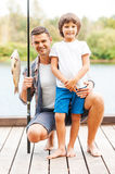 Look what we caught!. Father and son looking at camera and smiling while men holding fishing rod with big fish on the hook Stock Photos