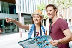 Look what we have there. Happy young couple as tourists with a map Stock Photo