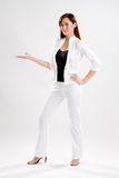 Look at what i have. Young business executive showing something in her right hand wearing a back and white top and pants Stock Photo