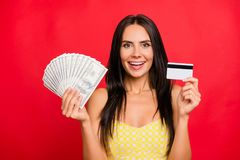 Look what I have! Close up portrait of cheerful joyful beautiful. With long dark hair boasting about earnings on the internet, withdraw money, isolated on red Stock Photo