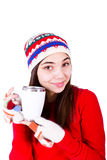 Look What my Company Gave me. Young girl in winter clothes holding a coffe cup with copy space on it. Wearing Winter hat and fingerless glowes. Isolated on white Royalty Free Stock Photos