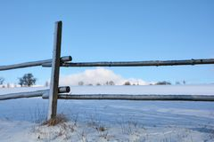 Look by a wooden fence on a field in winter with snow and blue sky Stock Images