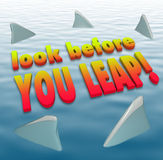 Look Before You Leap Warning Caution Saying Shark Fins. Look Before You Leap words on water surrounded by shark fins to illustrate a quote or saying of warning Royalty Free Stock Image