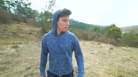 Look of the young man walking and looking around on the nature. Slowly stock video