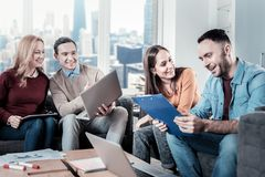 Satisfied smart company working in pairs and having fun. Look at this. Young satisfied smart company sitting in the office working in pairs and having fun Stock Image