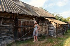 LookBook portrait of a girl in a rustic vintage dress with rakes near a rural barn and cowshed in a courtyard. LookBook portrait of a girl in a simple vintage stock photos